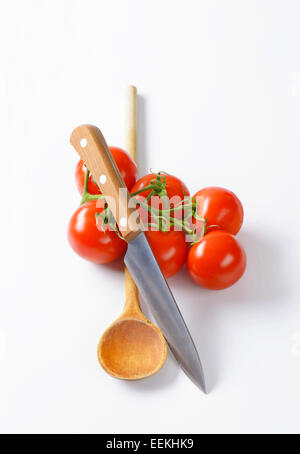 Frische rote Tomaten, Küchenmesser und Holzlöffel - Stockfoto