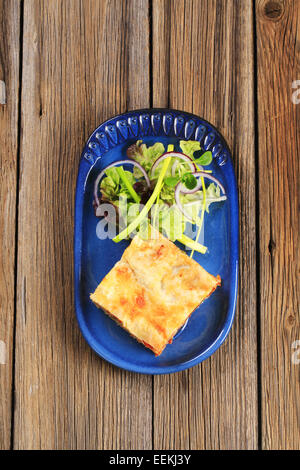 Portion Lasagne mit Salat garniert - Stockfoto
