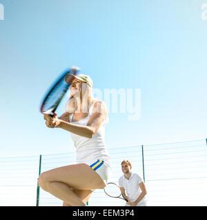 Jung verheiratet paar Tennis spielen in weißen Sportwear auf dem Tennisplatz draußen im Sommer - Stockfoto