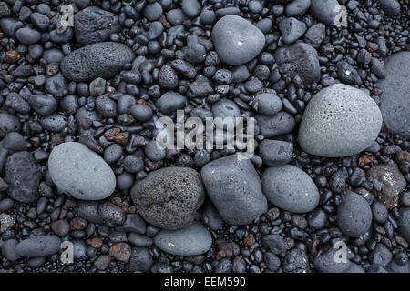 Schwarze Lavagestein der Brandung an der Küste, schwarze Kieselsteine mit runden Kanten, vulkanische Steine, in - Stockfoto