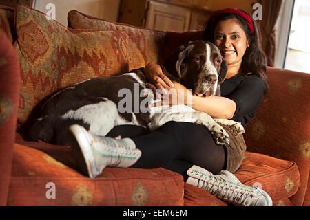 Frau sitzt auf der Couch mit ihrem Hund - Stockfoto