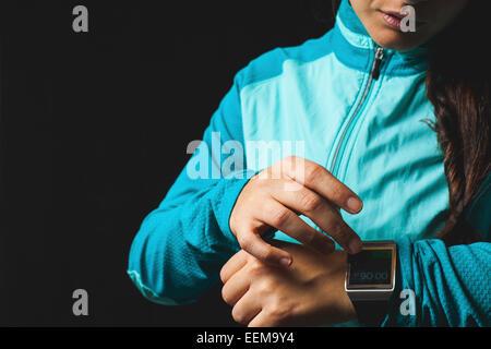 Frau trägt Smartwatch Gerät auf schwarzem Hintergrund - Stockfoto