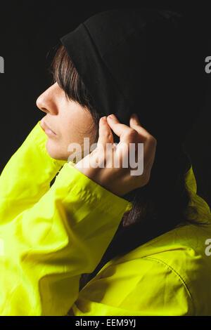 Porträt der jungen Frau mit gelben Regenmantel und Mütze Hut - Stockfoto