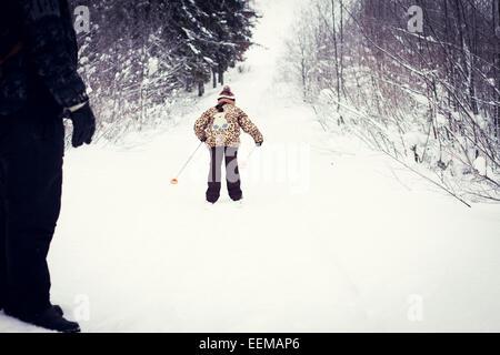 Kaukasische Vater und Tochter Langlaufen auf verschneiten Straße - Stockfoto