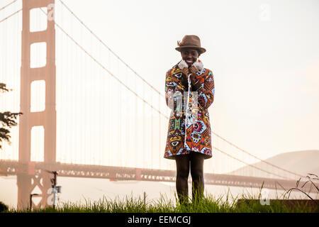 Schwarze Frau mit bunten Mantel von Golden Gate Bridge, San Francisco, California, Vereinigte Staaten von Amerika Stockfoto