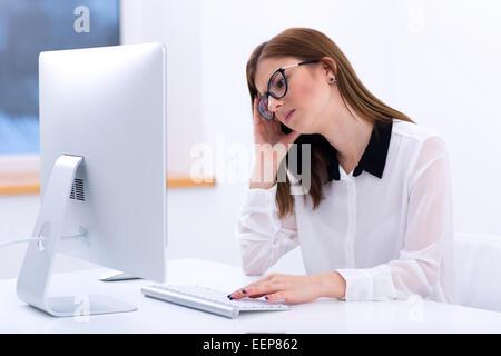 Müde Geschäftsfrau, die im Büro arbeiten - Stockfoto