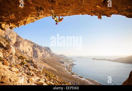 Männliche Kletterer Klettern auf einem Dach in einer Höhle bei Sonnenuntergang - Stockfoto