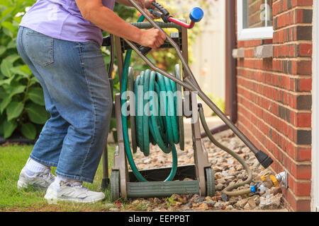 Frau mit Spina Bifida mit Krücken und ziehen Gartenschlauch - Stockfoto