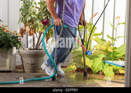 Frau mit Spina Bifida gehen mit Krücken und ziehen Gartenschlauch - Stockfoto