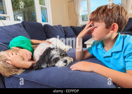 """Jungen mit Hörschädigungen Unterzeichnung """"Schlaf"""" in amerikanischer Gebärdensprache auf ihrer couch - Stockfoto"""