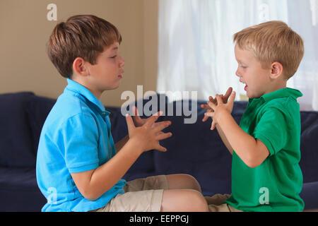 """Jungen mit Hörschädigungen Unterzeichnung """"Fußball"""" in amerikanischer Gebärdensprache auf ihrer couch - Stockfoto"""