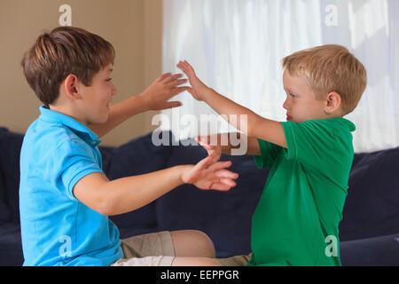 """Jungen mit Hörschädigungen Unterzeichnung """"sicher"""" in amerikanischer Gebärdensprache auf ihrer couch - Stockfoto"""