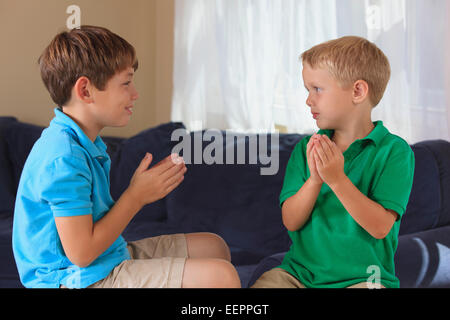 Jungen mit Hörschädigungen Unterzeichnung 'Boot' in amerikanischer Gebärdensprache auf ihrer couch - Stockfoto