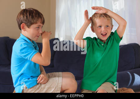 Jungen mit Hörschädigungen Unterzeichnung in der amerikanischen Gebärdensprache auf ihrer couch - Stockfoto