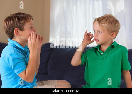 """Jungen mit Hörschädigungen Unterzeichnung """"Katze"""" in amerikanischer Gebärdensprache auf ihrer couch - Stockfoto"""