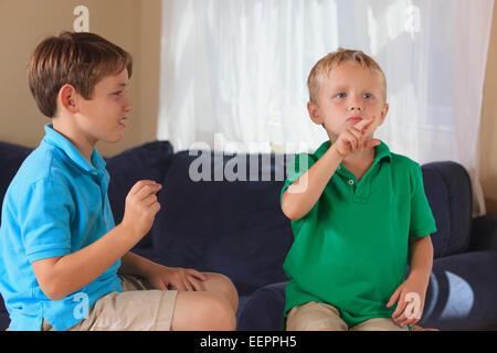 """Jungen mit Hörschädigungen Unterzeichnung """"Ente"""" in amerikanischer Gebärdensprache auf ihrer couch - Stockfoto"""