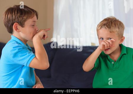 """Jungen mit Hörschädigungen Unterzeichnung """"Vogel"""" in amerikanischer Gebärdensprache auf ihrer couch - Stockfoto"""