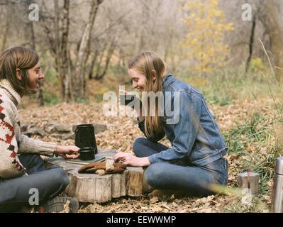 Lächelnde paar sitzen auf dem Boden in einem Wald, Kaffee zu trinken. - Stockfoto