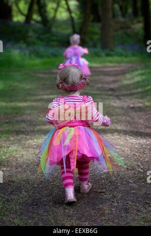 Zwei kleine Mädchen zu Fuß auf einem Weg im Frühling Wald. - Stockfoto