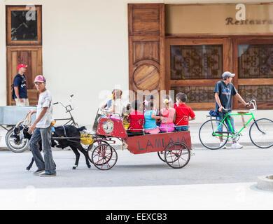 Eine Gruppe junger Kinder in einem Home-made Warenkorb durch eine Ziege in einer Straße in Camagüey, der drittgrößten - Stockfoto