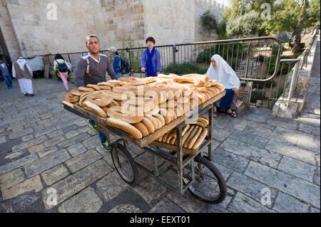 JERUSALEM, ISRAEL - 7. Oktober 2014: Ein Mann mit Brot auf seine Träger Dreirad in der Nähe von Damaskus-Tor in - Stockfoto