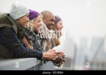 Freunde auf der Brücke stehen und lachen - Stockfoto