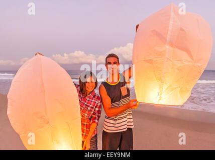 Junge Menschen mit beleuchteten Laternen am Strand - Stockfoto