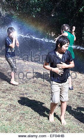 Ein Junge im Gesicht von einem Wasserstrahl schlagen, als Kinder die heißen, sonnigen Wetter, durch spielen und - Stockfoto