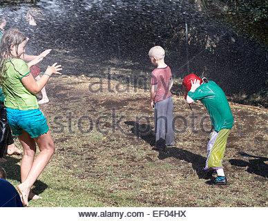 Ein Kind Krebs Patienten stehen immer noch, als er genießt das Wasser aus einem Schlauch mit anderen School Kids - Stockfoto