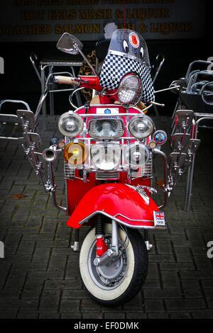 Ein roter Motorroller mit einer Reihe von Chrom Spiegel und Leuchten. - Stockfoto