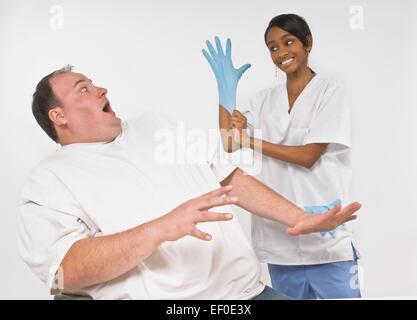 Ängstlich übergewichtiger Mann betrachtet man Krankenschwester - Stockfoto