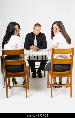 Zwei Frauen sitzen gegenüber dem Mann an der Rezeption - Stockfoto