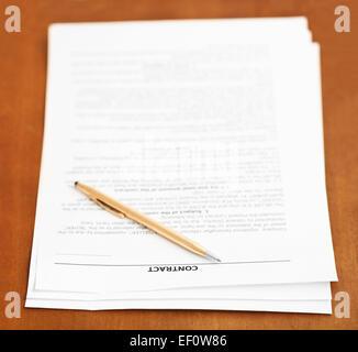drei Seiten des Kaufvertrages und goldener Kugelschreiber auf Holztisch - Stockfoto