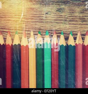 Reihe von farbigen Zeichnung Bleistifte Closeup auf alten Schreibtisch. Vintage stilisierte Abbildung. - Stockfoto