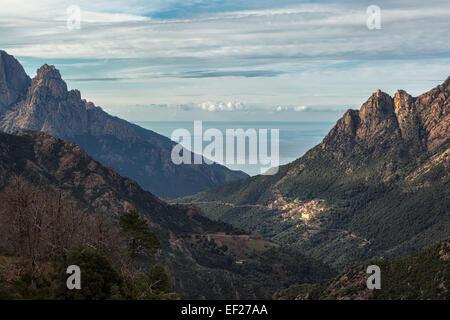Das Dorf Ota in Korsika mit Bergen und dem Mittelmeer hinter - Stockfoto