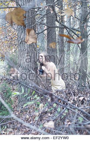 Ziemlich kaukasischen Frau in ein blasses gold Kleid hockt in der Nähe eines Baumes im Wald an einem windigen Herbsttag - Stockfoto