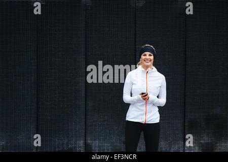 Porträt der glückliche junge Frau anhören von Musik auf dem Handy. Weibliche Läufer entspannend nach einer Trainingseinheit. - Stockfoto