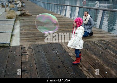 Kleines Mädchen auf der Suche in einer riesigen Seifenblase bestaunen, während ihre Mutter aussieht, Vancouver, - Stockfoto