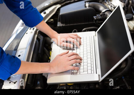 Mechaniker mit Laptop im Auto - Stockfoto