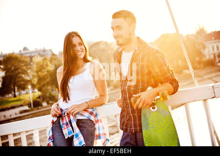 Junges Paar mit Skateboard auf Brücke - Stockfoto