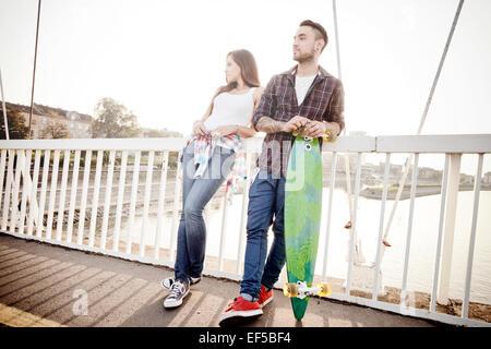 Junges Paar mit Skateboard warten auf Brücke - Stockfoto
