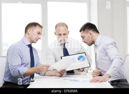 ernsthafte Geschäftsleute mit Papieren im Büro - Stockfoto