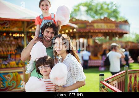 Porträt von fröhlichen Familienholding rosa Zuckerwatte im Vergnügungspark - Stockfoto