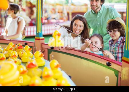 Eltern mit zwei Kindern Spaß mit Angelspiel im Vergnügungspark - Stockfoto