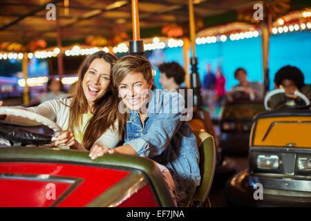 Zwei fröhliche Frauen auf Autoscooter fahren im Freizeitpark - Stockfoto