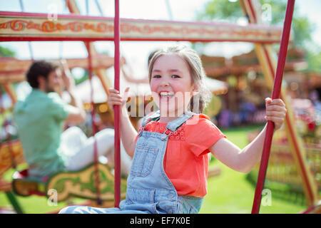 Fröhliches Mädchen lachend auf Karussell im Vergnügungspark - Stockfoto