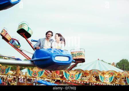 Paar genießt Reiten auf Karussell im Vergnügungspark - Stockfoto