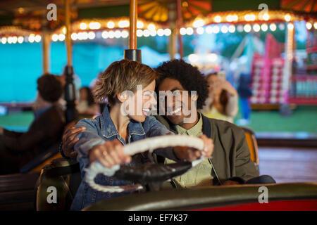 Junges Paar auf Autoscooter Fahrt im Vergnügungspark - Stockfoto