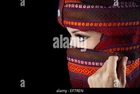 Orientalische Frau mit Turban bedeckt ihr Gesicht auf schwarzem Hintergrund Stockfoto