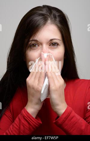 Junge Frau in roten Bluse, die ihre Nase mit Seidenpapier - Stockfoto